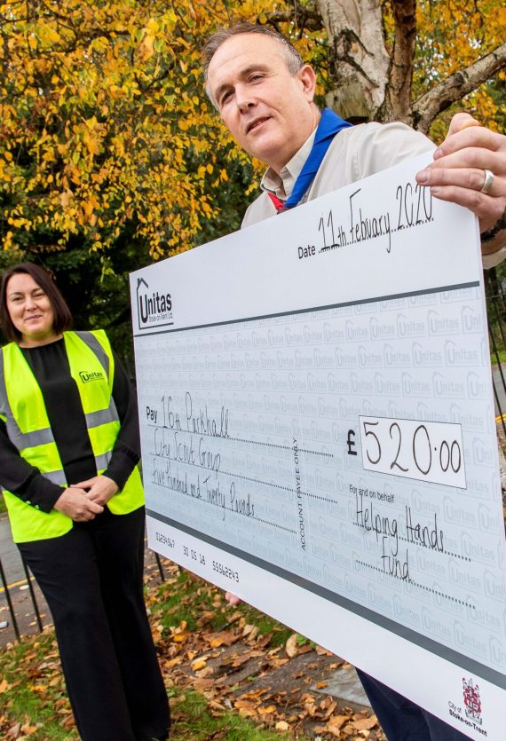 Parkhall City Scout Group Worker holding check from unitas
