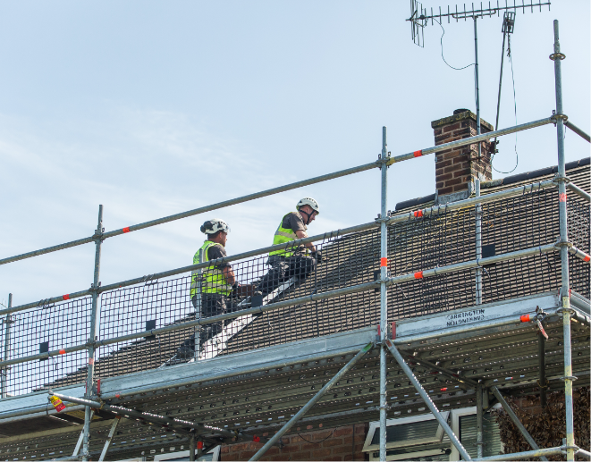 Unitas workers on a house roof